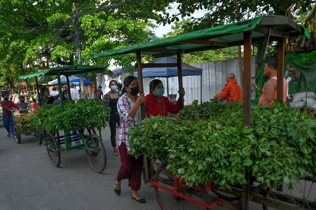 """People push carts with vegetables for distribution during a """"Donate your extras, take what you need"""" donation drive aimed at helping low income households in Thaketa township in Yangon on April 6, 2021, as communities cope with an economic downturn in Myanmar amid widespread protests against the military coup. (Photo by AFP Photo/Stringer)"""
