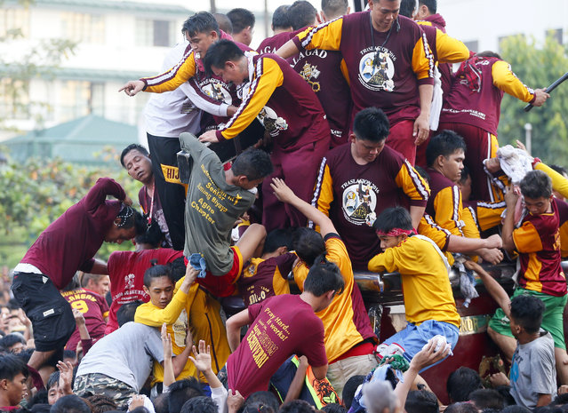 A few Catholic devotees manage to get closer to either kiss or rub with towels, the cross of the image of the Black Nazarene as they take part in a raucous procession to celebrate its feast day in Manila, Philippines, Saturday, January 9, 2016. (Photo by Bullit Marquez/AP Photo)