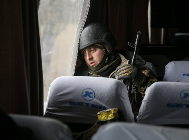 A Ukrainian serviceman who fought in Debaltseve is seen in a bus before leaving for his home, near Artemivsk February 19, 2015. (Photo by Gleb Garanich/Reuters)