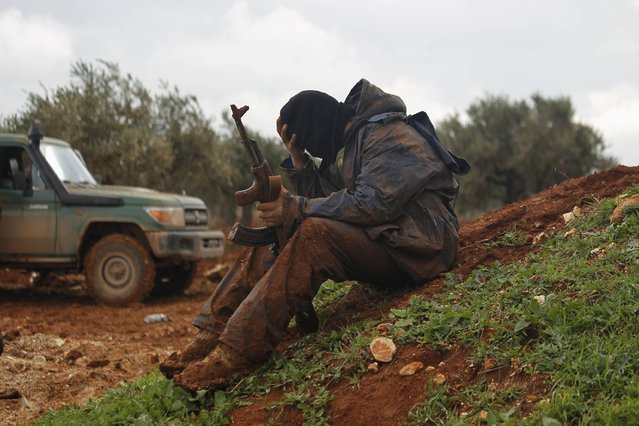 A rebel fighter of al-Jabha al-Shamiya (the Shamiya Front) covered with mud carries his weapon as he sits near the front line with Bashkuwi village, north of Aleppo February 19, 2015. Battles in and around the Syrian city of Aleppo have killed at least 70 pro-government fighters and more than 80 insurgents after the army launched an offensive there, a monitoring group said on Wednesday. (Photo by Rami Zayat/Reuters)