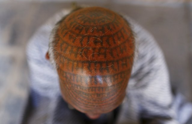 Chanda Ram, 72, a follower of Ramnami Samaj, who has tattooed the name of the Hindu god Ram on his entire face and head, poses for a picture inside his house in the village of Chapora, in the eastern state of Chhattisgarh, India, November 15, 2015. (Photo by Adnan Abidi/Reuters)