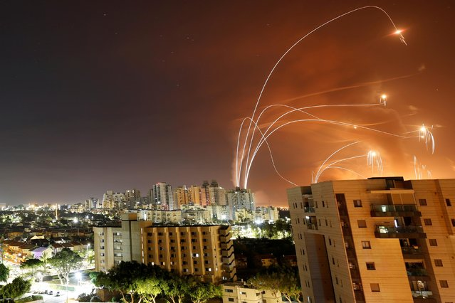 Streaks of light are seen as Israel's Iron Dome anti-missile system intercept rockets launched from the Gaza Strip towards Israel, as seen from Ashkelon, Israel on May 12, 2021. (Photo by Amir Cohen/Reuters)