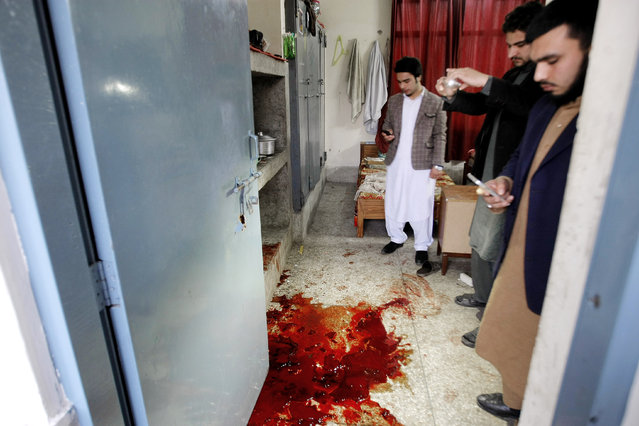 Pakistani students look at a pool of blood following an attack at Bacha Khan University in Charsadda town, some 35 kilometers (21 miles) outside the city of Peshawar, Pakistan, Wednesday, January 20, 2016. Gunmen stormed Bacha Khan University named after the founder of an anti-Taliban political party in the country's northwest Wednesday, killing many people, officials said. (Photo by Mohammad Sajjad/AP Photo)