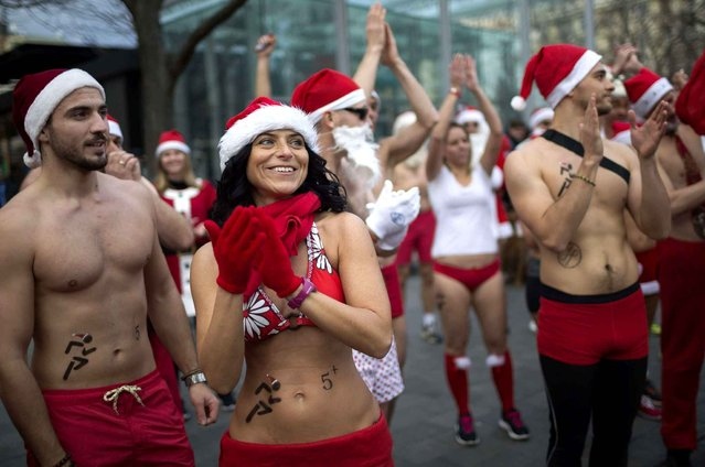 A group of people wearing Santa Claus hats and swimming suits participate in the 13th charity Great Santa Claus Run in downtown Budapest, Hungary, Sunday, December 11, 2016. (Photo by Balazs Mohai/MTI via AP Photo)