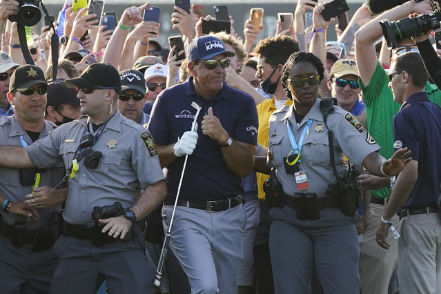 Phil Mickelson makes his way through fans on the 18th fairway during the final round at the PGA Championship golf tournament on the Ocean Course, Sunday, May 23, 2021, in Kiawah Island, S.C. (Photo by Matt York/AP Photo)