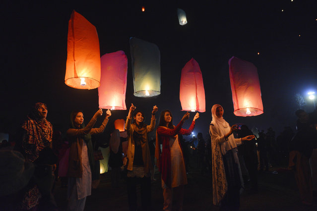 Pakistani civil society activists release lanterns into the sky in Lahore on December 15, 2016, as they pay tribute to victims on the second anniversary of an attack on The Army Public School in the city of Peshawar. Taliban militants attacked on Pakistani Army Public School in Peshawar, killing 151 people mostly children on December 16, 2014. (Photo by Arif Ali/AFP Photo)