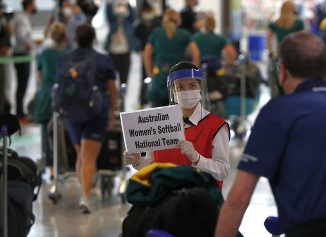 A woman wearing protective mask and face shield greets members of Australia's Olympic softball squad on their arrival at Narita international airport in Narita, east of Tokyo, Japan Tuesday, June 1, 2021. Australia's Olympic softball squad touched down in Japan on Tuesday and was among the earliest arrivals for the Tokyo Games. (Photo by Issei Kato/Pool Photo via AP Photo)