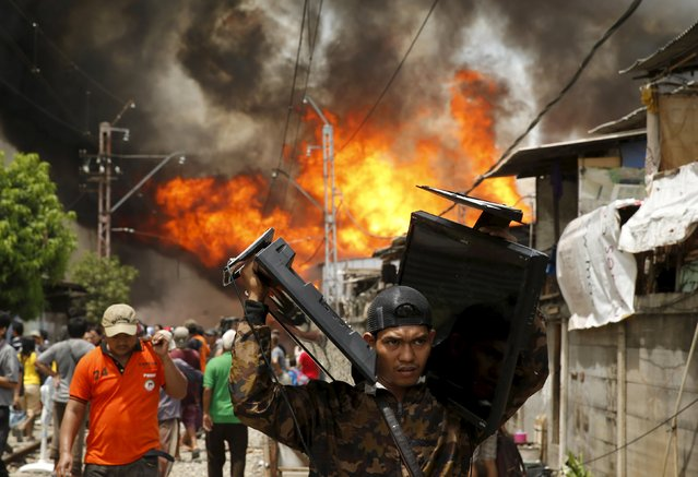 A man carries two televisions away from a fire in a slum area next to railway tracks in Kampung Bandan, North Jakarta, Indonesia  January 26, 2016. According to local media, the fire destroyed approximately 100 wooden dwellings, built along a busy railway line. No casualties were reported. (Photo by Reuters/Beawiharta)