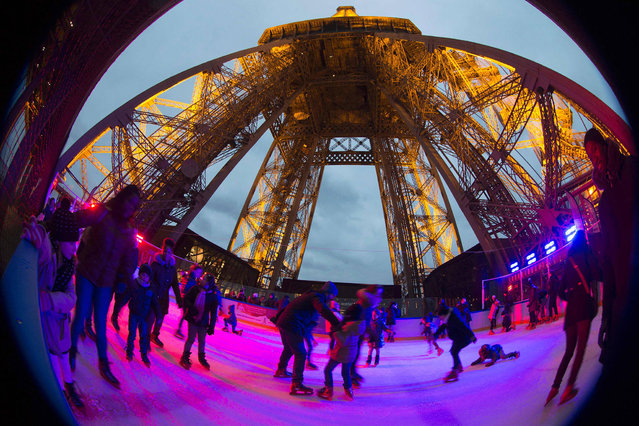 People enjoy skating at the open air Christmas ice rink on the first floor of the Eiffel Tower after its reopening on December 19, 2016 in Paris The ice rink of about 200 square metres and on the first floor of the tower (57 metres above the ground) is open to the public until February 19, 2017. (Photo by Joel Saget/AFP Photo)