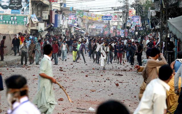 Pakistani protesters throw rocks during clashes with police to condemn Sunday's suicide bombings that struck two churches, in Lahore, Pakistan, Monday, March 16, 2015. Pakistani police fired tear gas on Monday after Christian protesters clashed with police in the eastern city of Lahore, a day after Taliban bombers killed more than a dozen people in suicide attacks on two churches in the city. (Photo by K. M. Chaudary/AP Photo)