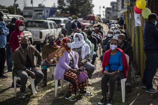 Ethiopians queue on chairs in the street as they wait to cast their votes in the general election at a polling center in the capital Addis Ababa, Ethiopia, Monday, June 21, 2021. Ethiopia was voting Monday in the greatest electoral test yet for Prime Minister Abiy Ahmed as insecurity and logistical issues meant ballots wouldn't be cast in more than 100 constituencies of the 547 across the country. (Photo by Ben Curtis/AP Photo)