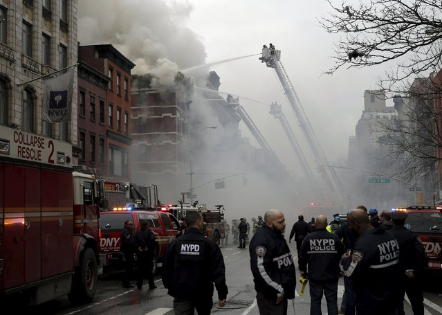 New York City Fire Department firefighters and police stand by as firefighters fight a fire at a residential apartment building in New York City March 26, 2015. (Photo by Mike Segar/Reuters)