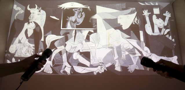 """People aim flashlights at a projected image of """"Guernica"""" from 1937 by Spanish artist Pablo Picasso at the exhibition """"Picasso and the Spanish Modernity"""" at Centro Cultural Banco do Brazil in Sao Paulo March 25, 2015. (Photo by Paulo Whitaker/Reuters)"""
