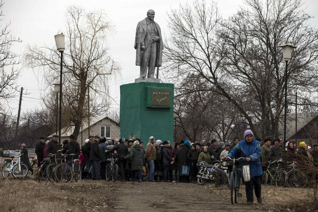 People queue for free food distributed by pro-Russian rebels next to a monument of the Soviet state founder Vladimir Lenin in the village of Chornukhyne near the town of Debaltseve, north-east from Donetsk, March 12, 2015. (Photo by Marko Djurica/Reuters)