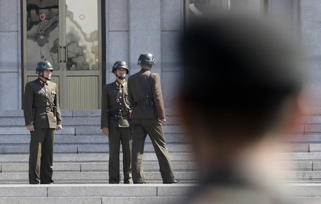 In this April 18, 2018 file photo, three North Korean soldiers talk each others as a South Korean soldier, right, stands at the border village of Panmunjom in the Demilitarized Zone, South Korea. North and South Korea began removing mines at two sites inside their heavily fortified border Monday, October 1, 2018, as part of their recent deals to ease decades-long military tensions. The mine removal took place at the Koreas' Joint Security Area in their shared border village of Panmunjom and another front-line area where the two countries plan their first joint searches for the remains of soldiers killed during the 1950-53 Korean War. (Photo by Lee Jin-man/AP Photo)