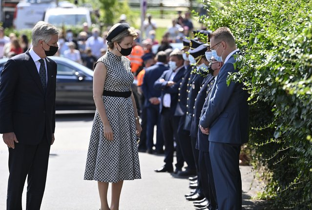 Belgium's King Philippe, left, and Belgium's Queen Mathilde, second left, speak with emergency workers prior to one minute of silence to pay respect to victims of the recent floods in Belgium, in Verviers, Belgium, Tuesday, July 20, 2021. Belgium is holding a day of mourning on Tuesday to show respect to the victims of the devastating flooding last week, when massive rains turned streets in eastern Europe into deadly torrents of water, mud and flotsam. (Photo by Eric Lalmand/Pool Photo via AP Photo)