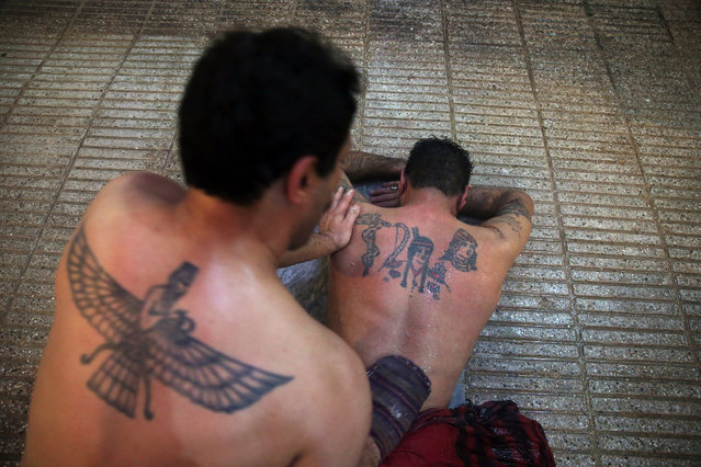 In this Friday, January 9, 2015 photo, bathhouse worker Omid Riahi, 39, scrubs a man to remove dead skin, at the Ghebleh public bathhouse, in Tehran, Iran. The steamy air and curved tiled walls of Iran's famed public bathhouses, some rinsing and massaging patrons for hundreds of years, slowly may wash away as interest in them wanes. (Photo by Ebrahim Noroozi/AP Photo)