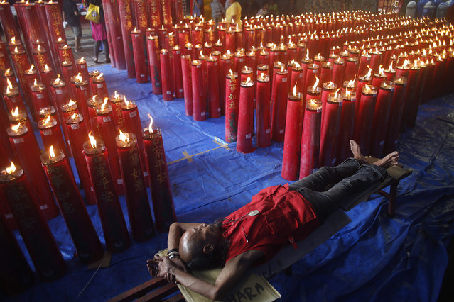 An Indonesian ethnic Chinese worker takes a nap beside candles during the Chinese New Year celebrations at a temple in Bogor, Indonesia, 08 February 2016. China's Lunar New Year begins on 08 February 2016. (Photo by Adi Weda/EPA)