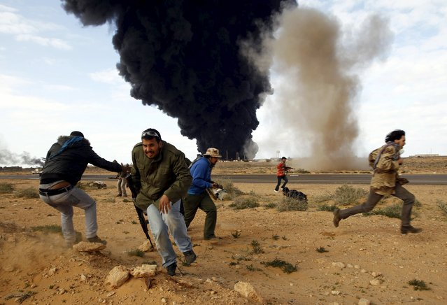 Rebel fighters run for cover in front of a burning gas storage terminal during a battle on the road between Ras Lanuf and Bin Jawad, March 9, 2011. (Photo by Goran Tomasevic/Reuters)