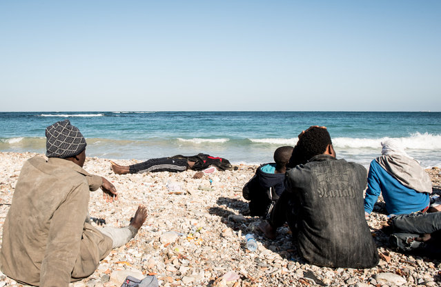 The body of a migrant is seen as other surviving migrants, who were on a boat which capsized on Wednesday, sit on a beach after police arrested them in Tripoli, Libya, January 4, 2017. (Photo by Reuters/Stringer)