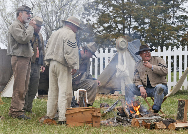 Confederate Civil War re-enactors gather around their campfire as part of the commemoration of the 150th anniversary of the surrender of the Army of Northern Virginia at Appomattox Court House in Appomattox, Va., Thursday, April 9, 2015. (Photo by Steve Helber/AP Photo)