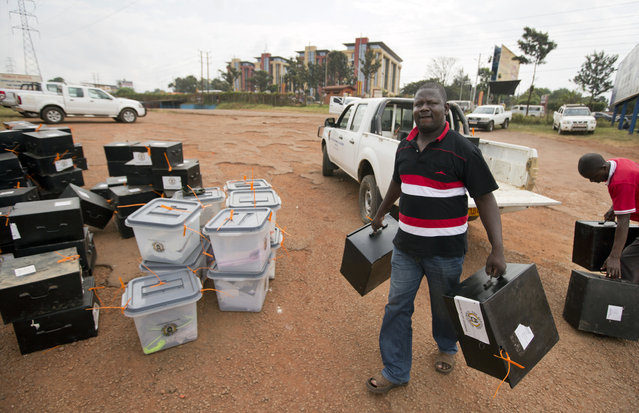 An electoral worker delivers boxes to a district counting center in Kampala, Uganda Saturday, February 20, 2016. As Ugandans await the final results of Thursday's election, which are due to be announced later on Saturday, the main opposition candidate Kizza Besigye remained under house arrest after his party headquarters were raided and he was detained by police on Friday. (Photo by Ben Curtis/AP Photo)