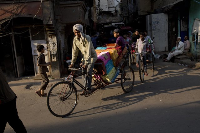 A rickshaw driver transports goods in the old Delhi area of New Delhi, India, Tuesday, April 14, 2015. The four-century-old neighborhood is chaotic and crowded, yet is the vibrant heart of the city. (Photo by Bernat Armangue/AP Photo)