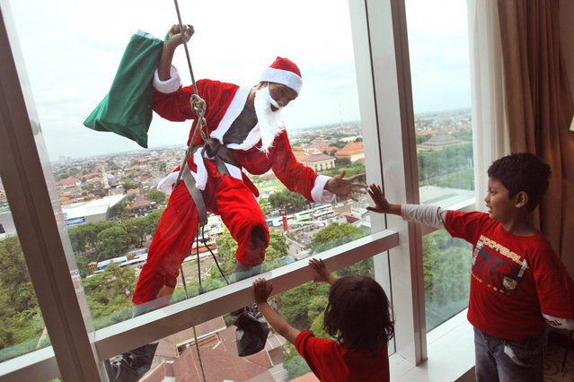 An employee in Santa outfit greets children as he rappels down from the roof of a hotel during a promotional event to celebrate Christmas in Surabaya, East Java, Indonesia, Monday, December 23, 2013. (Photo by AP Photo/Trisnadi)
