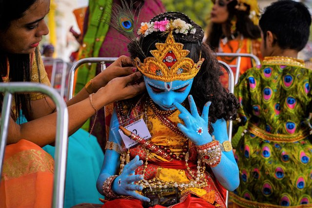 """A child dressed as Hindu god Krishna watches a mobile phone as a woman gives finishing touches to his costume on the occasion of """"Janmashtami"""" festival marking the birth of Krishna in Ajmer on August 30, 2021. (Photo by Himanshu Sharma/AFP Photo)"""