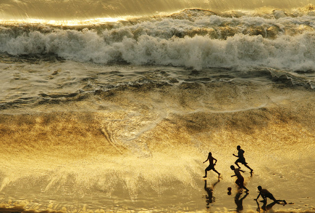 Children play soccer during sunset at a beach in Lima, Peru, December 26, 2008. (Photo by Enrique Castro-Mendivil/Reuters)