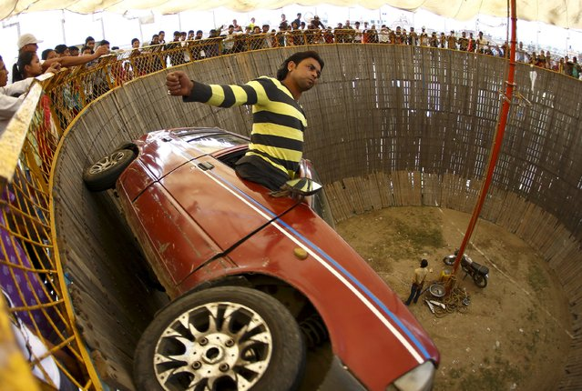 "A stuntman performs while riding a car inside the ""Well of Death"" attraction during a fair in Bhaktapur April 20, 2015. (Photo by Navesh Chitrakar/Reuters)"
