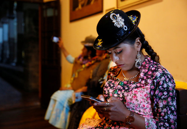 A Cholita (Andean woman) model handles her mobile phone after a practice session at the Rosario Aguilar fashion model school in La Paz, Bolivia, February 23, 2019. (Photo by David Mercado/Reuters)