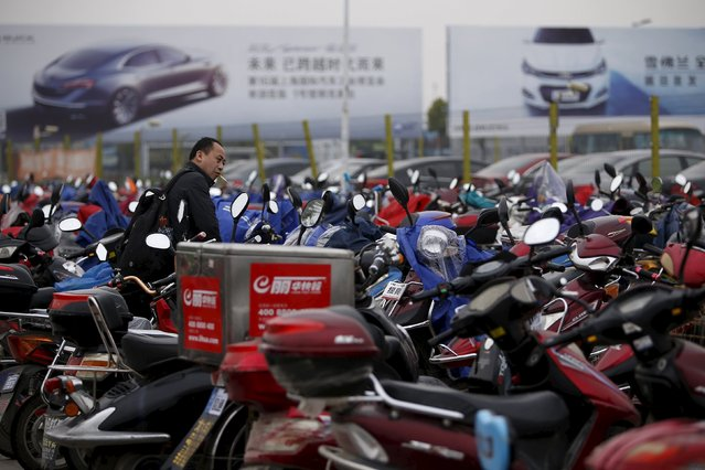 A man parks his electric bicycle in front of GM car advertisements outside the 16th Shanghai International Automobile Industry Exhibition in Shanghai, April 20, 2015. Foreign automakers continue to plough money into factories in China, the world's largest car market, even as the biggest economic slowdown in a quarter of a century crimps sales growth. (Photo by Aly Song/Reuters)