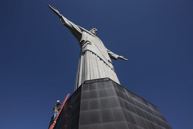 A worker climbs the Christ Redeemer statue to examine recent damage in Rio de Janeiro, Brazil, Tuesday, Jan. 21, 2014. (Photo by Felipe Dana/AP Photo)