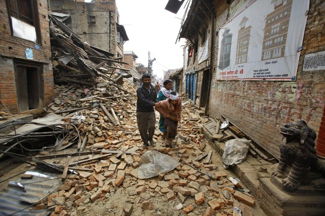 An elderly injured woman is taken home through earthquake debris after treatment in Bhaktapur near Kathmandu, Nepal, Sunday, April 26, 2015. (Photo by Niranjan Shrestha/AP Photo)
