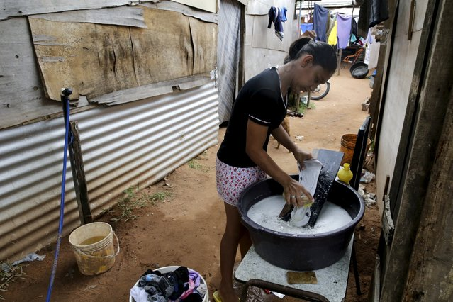 A woman washes clothes during International Women's Day in Asuncion, Paraguay March 8, 2016. (Photo by Jorge Adorno/Reuters)