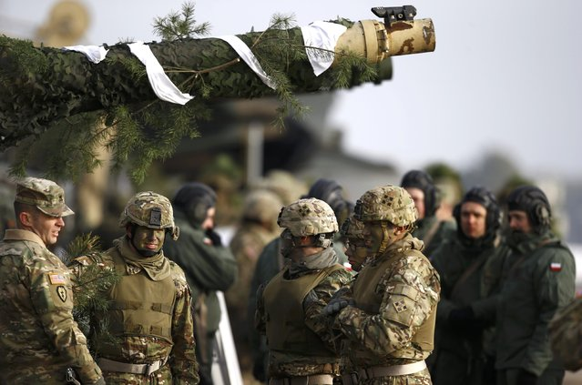 U.S. and Polish army soldiers gather near their tanks after live firing exercise in Zagan, Poland, January 30, 2017. (Photo by Kacper Pempel/Reuters)