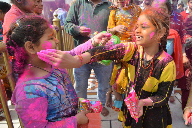 Indian devotees play with coloured powder as they celebrate the Holi festival at a temple in Amritsar on March 20, 2019. Holi, the popular Hindu spring festival of colours is observed in India at the end of the winter season on the last full moon of the lunar month. (Photo by Narinder Nanu/AFP Photo)