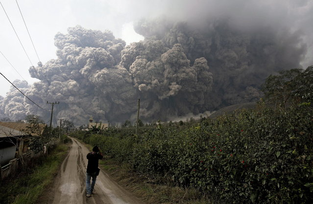 An Indonesian journalist looks at the mounth Sinabung spewing volcanic materials in Karo, North Sumatra, Indonesia, 01 February 2014. At least 14 people were killed when a volcano on the Indonesian island of Sumatra spewed lava and hot gas, an aid worker said. The eruption of Mount Sinabung came a day after the National Disaster Management Agency said residents living farther than 5 kilometres from the peak were being allowed to return to their homes after a lull in activity. (Photo by Chairaly/EPA)