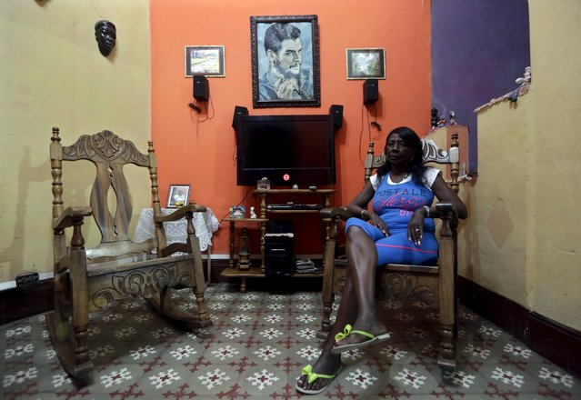 """Reina, 54, sits in the living room of her house with a picture of revolutionary fighter Ernesto """"Che"""" Guevara hanging on the wall in Havana February 21, 2016. (Photo by Enrique de la Osa/Reuters)"""