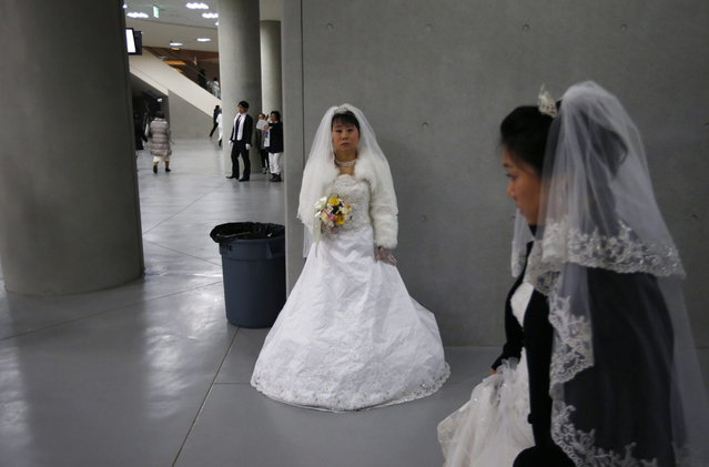 A bride waits for her groom during a mass wedding ceremony of the Unification Church at Cheongshim Peace World Centre in Gapyeong, about 60 km (37 miles) northeast of Seoul February 12, 2014. (Photo by Kim Hong-Ji/Reuters)