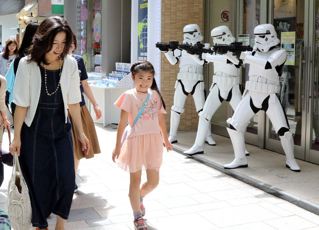 "Pedestrians pass before Storm Troopers at a toy shop in Tokyo on May 4, 2015. May 4th is called the Star Wars Day among Star Wars fans as the famous phrase ""May the Force be with you"" in the movie sounds like ""May the 4th be with you"". (Photo by Yoshikazu Tsuno/AFP Photo)"