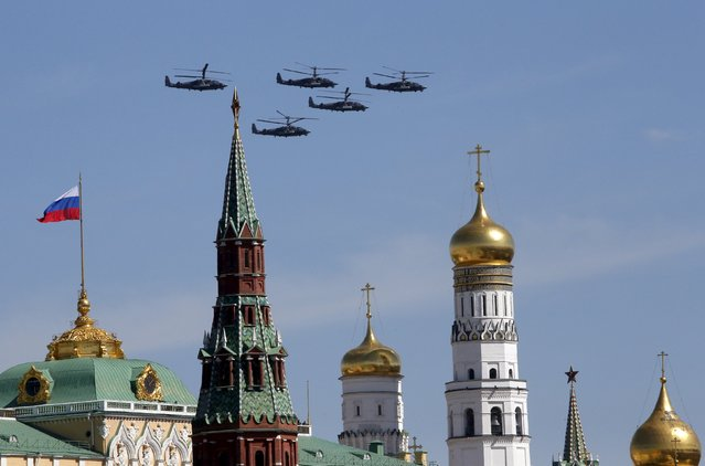 """Ka-52 """"Alligator"""" military helicopters fly in formation above Red Square and the Kremlin during a rehearsal for the Victory Day parade in central Moscow, Russia, May 7, 2015. (Photo by Maxim Zmeyev/Reuters)"""