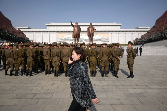 "A woman talks on a mobile phone as Korean Peole's Army (KPA) soldiers arrive to pay their respects before the statues of late North Korean leaders Kim Il Sung and Kim Jong Il, as part of celebrations marking the anniversary of the birth of Kim Il Sung, known as the ""Day of the Sun"", on Mansu hill in Pyongyang on April 15, 2019. (Photo by Ed Jones/AFP Photo)"