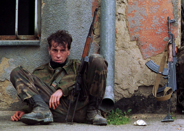 """A weary soldier of the Bosnian Army Fifth Corps' elite 502 """"Tigers"""" brigade rests against a wall before heading home after his unit captured a strategic town from separatist Serb forces, securing a road that led into Sarajevo, October 1995. (Photo by Chris Helgren/Reuters)"""