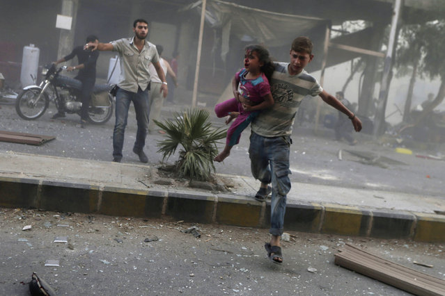 A man carries an injured girl after what activists said were five air strikes by forces loyal to Syria's President Bashar al-Assad in Douma, eastern al-Ghouta, near Damascus September 11, 2014. (Photo by Bassam Khabieh/Reuters)
