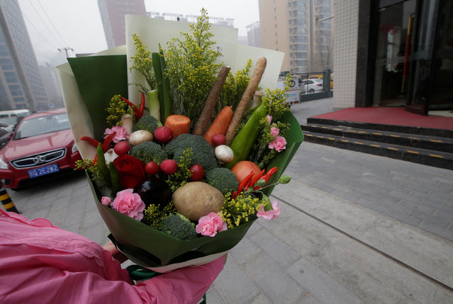 A woman receives a bouquet made of vegetables and flowers, priced at 238RMB, from a delivery staff of a florist outside an office building on Valentine's Day in Beijing, China, February 14, 2017. (Photo by Jason Lee/Reuters)