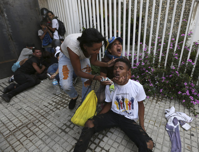 An anti-government protester calls for help as she and another woman help a fellow demonstrator who has been overcome by teargas during clashes with security forces, in Caracas, Venezuela, Wednesday, May 1, 2019. Opposition leader Juan Guaidó called for Venezuelans to fill streets around the country Wednesday to demand President Nicolás Maduro's ouster. Maduro is also calling for his supporters to rally. (Photo by Fernando Llano/AP Photo)