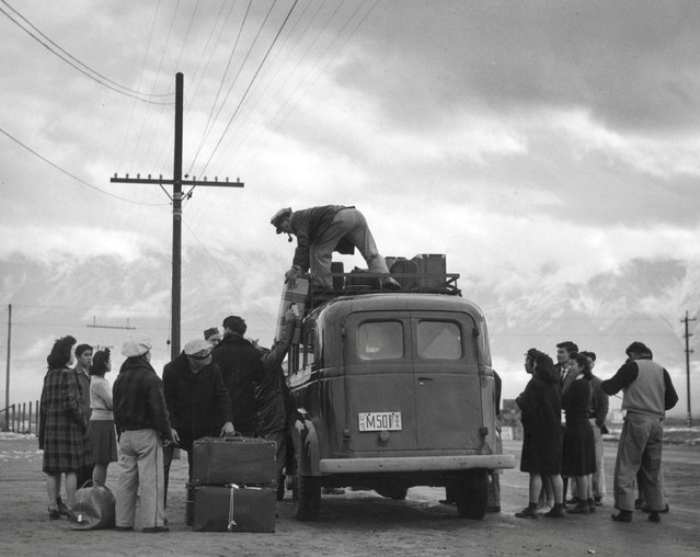 People of Japanese ancestry load a bus heading to the Manzanar War Relocation Center in California, 1943. (Photo by Courtesy Ansel Adams/Library of Congress, Prints and Photographs Division/Reuters)