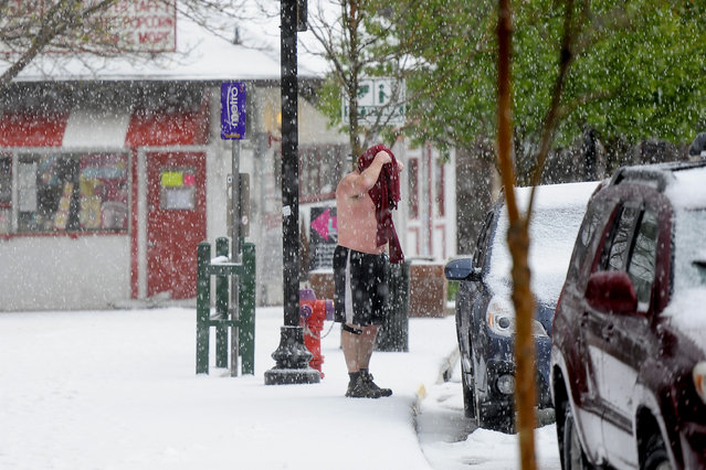 A man changes into a dry shirt after about two inches of hail fell on Manitou Springs, Colo. during a large thunderstorm Saturday, May 9, 2015. (Photo by Michael Ciaglo/AP Photo/The Gazette)
